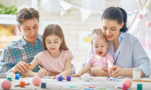 Happy family. Mother, father and daughters painting together. Adults helping to children girls.